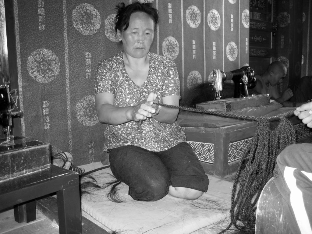 Monkhtsetseg, working with speed and precision, spent many hours plaiting lustrous horse mane hair (never from the tail) into lengths of rope that still connect trellises supporting the walls of the Shining White Palace Ger at DC. This was one of her contributions to the collaborative rebuilding effort. Once cut, the horses' hair had been meticulously cleaned, teased out and separated into smaller workable lots. The young lams, women and men all pitched in to do this very time-consuming preparatory work together. The joy of shared purpose and endeavor was palpable. Delgeruun Choira in the Dundgovi, Mongolia 25 July 2005. Photograph: C.Pleteshner